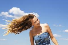 Chica joven que sacude su cabeza sobre fondo del cielo azul Imagen de archivo