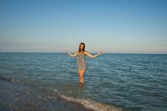 Chica joven que salpica el agua en el mar Fotografía de archivo