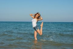 Chica joven que salpica el agua en el mar Fotos de archivo libres de regalías