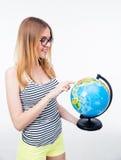 Chica joven que señala el finger en el globo del mundo Imagen de archivo