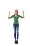 Chica joven que señala en un espacio de la copia mientras que presenta en la cámara i Foto de archivo