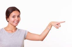 Chica joven que señala a su izquierda Imagen de archivo