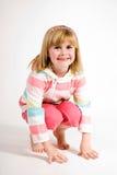 Chica joven que se agacha Foto de archivo libre de regalías