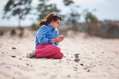 Chica joven que se arrodilla en la playa Foto de archivo libre de regalías