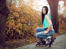 Chica joven que se arrodilla en pcteres de ruedas Fotografía de archivo