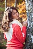 Chica joven que se coloca cerca del árbol en parque hermoso del otoño Fotos de archivo libres de regalías