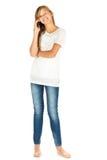 Chica joven que se coloca con el teléfono móvil sobre el fondo blanco Fotos de archivo libres de regalías