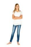 Chica joven que se coloca con la camiseta y los tejanos blancos sobre blanco Imágenes de archivo libres de regalías