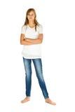Chica joven que se coloca con la camiseta y los tejanos blancos sobre blanco Fotos de archivo