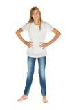 Chica joven que se coloca con la camiseta y los tejanos blancos sobre blanco Foto de archivo