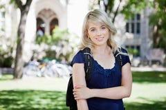 Chica joven que se coloca en el campus Fotografía de archivo