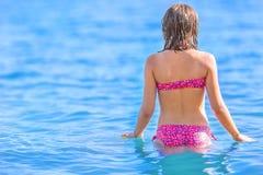Chica joven que se coloca en el mar antes de nadar Imagen de archivo