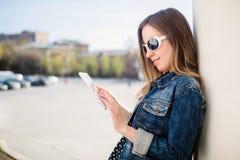 Chica joven que se coloca en estudiar de la yarda del campus de la universidad Imágenes de archivo libres de regalías