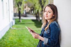 Chica joven que se coloca en la yarda del campus de la universidad con la tableta Fotos de archivo libres de regalías