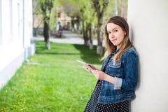 Chica joven que se coloca en la yarda del campus de la universidad con la tableta Imagen de archivo libre de regalías