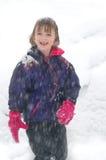 Chica joven que se coloca en nieve con caer de la nieve Imagen de archivo
