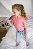 Chica joven que se coloca en su cama Fotografía de archivo libre de regalías