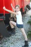 Chica joven que se coloca en un tren Imagenes de archivo