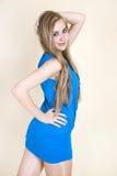 Chica joven que se coloca en una alineada azul Imagen de archivo