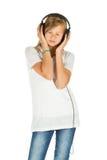Chica joven que se coloca que escucha la música sobre el fondo blanco Fotos de archivo