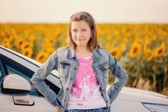 Chica joven que se coloca que se inclina en un coche Imagen de archivo libre de regalías