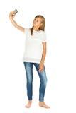 Chica joven que se coloca que toma un selfie sobre el fondo blanco Foto de archivo