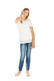 Chica joven que se coloca que toma un selfie sobre el fondo blanco Fotos de archivo