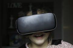 Chica joven que se divierte en casa con las auriculares de VR Imagen de archivo