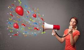 Chica joven que se divierte, gritando en el megáfono con los globos Imagen de archivo
