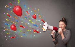 Chica joven que se divierte, gritando en el megáfono con los globos Fotos de archivo
