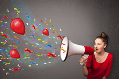 Chica joven que se divierte, gritando en el megáfono con los globos Imagenes de archivo