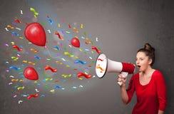 Chica joven que se divierte, gritando en el megáfono con los globos Fotos de archivo libres de regalías