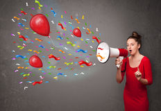 Chica joven que se divierte, gritando en el megáfono con los globos Imágenes de archivo libres de regalías