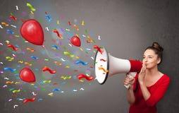Chica joven que se divierte, gritando en el megáfono con los globos Fotografía de archivo