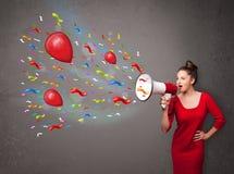 Chica joven que se divierte, gritando en el megáfono con los globos Foto de archivo