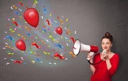 Chica joven que se divierte, gritando en el megáfono con los globos Foto de archivo libre de regalías