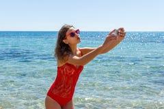 Chica joven que se divierte que toma imágenes del selfie del smartphone de sí misma Días de fiesta del viaje Fotos de archivo