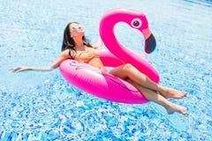 Chica joven que se divierte y que ríe y que se divierte en la piscina en un flamenco rosado inflable en un bañador y gafas de sol imágenes de archivo libres de regalías