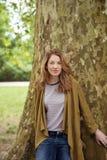 Chica joven que se inclina contra tronco de árbol grande Imagenes de archivo