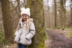 Chica joven que se inclina contra un árbol por una trayectoria en un bosque Foto de archivo