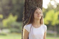 Chica joven que se inclina en un árbol Fotos de archivo libres de regalías