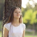Chica joven que se inclina en un árbol Imágenes de archivo libres de regalías