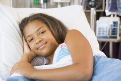 Chica joven que se reclina en cama de hospital Imágenes de archivo libres de regalías