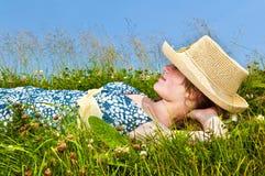 Chica joven que se reclina en prado fotos de archivo