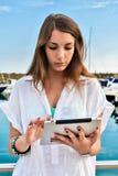 Chica joven que se relaja con la tableta en el muelle Fotografía de archivo
