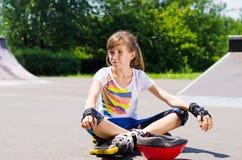 Chica joven que se relaja con su engranaje patinador Imagen de archivo