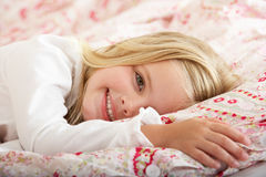 Chica joven que se relaja en cama Foto de archivo