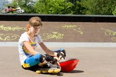 Chica joven que se relaja en el parque del patín Imagenes de archivo