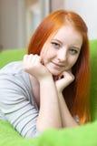 Chica joven que se relaja en el sofá Fotografía de archivo