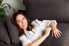 Chica joven que se relaja en el sofá en casa Imagen de archivo libre de regalías